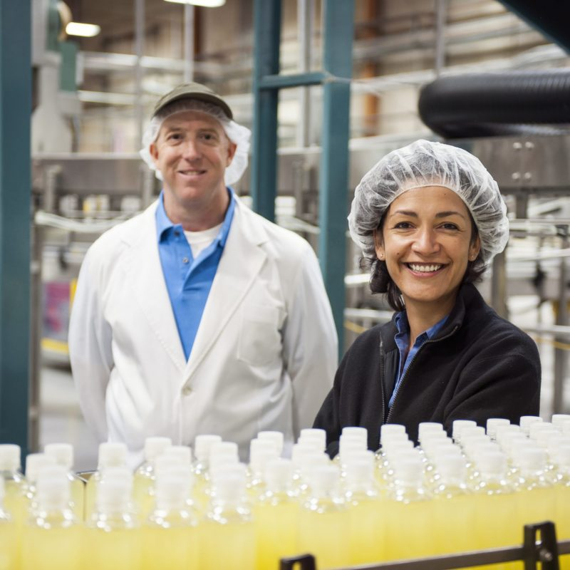 Portrait of a Caucasian male and African American female team of workers wearing head nets and standing near a conveyor belt of lemon flavored water in a bottling plant.